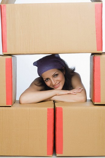 Portrait of a woman leaning on cardboard boxes : Stock Photo