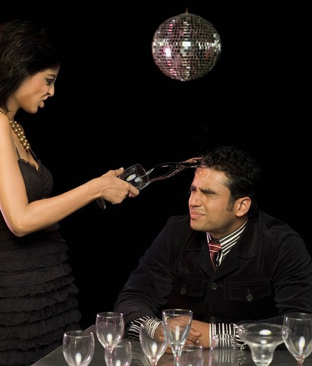 Woman throwing wine over man´s face : Stock Photo