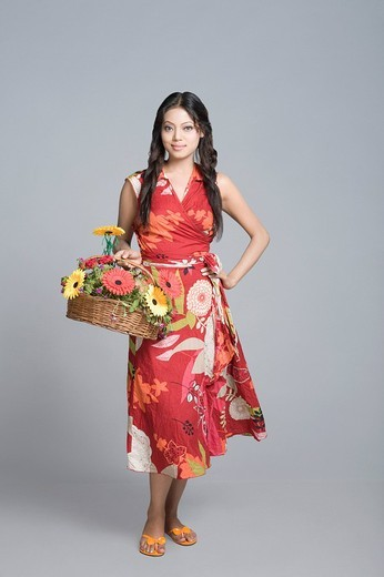 Portrait of a beautiful fashion model holding a basket of flowers : Stock Photo