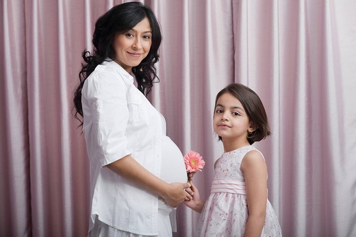 Girl giving a flower to her pregnant mother : Stock Photo