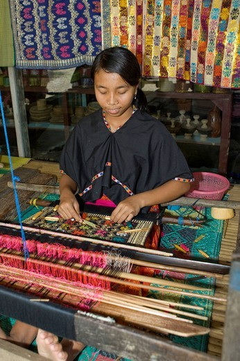 Woman weaving cloth in the traditional method on an old loom, Tete Batu, Lombok Island, Lesser Sunda Islands, Indonesia : Stock Photo