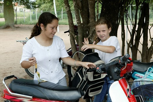 Girls with moped, Mennonite colony, Loma Plata, Chaco, Paragua, South America : Stock Photo