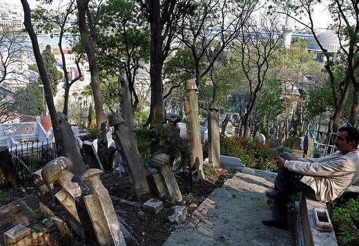 Man taking a break on an old Muslim cemetery in Eyuep, Golden Horn, Istanbul, Turkey : Stock Photo