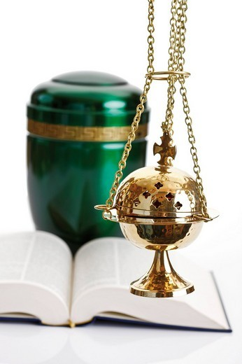 Opened Bible and an incense burner in front of a green urn : Stock Photo