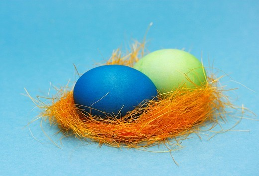 Two pastel_coloured Easter eggs in a nest : Stock Photo