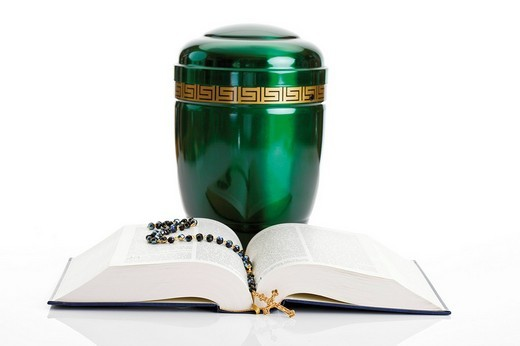 Opened Bible and rosary set in front of a green urn : Stock Photo