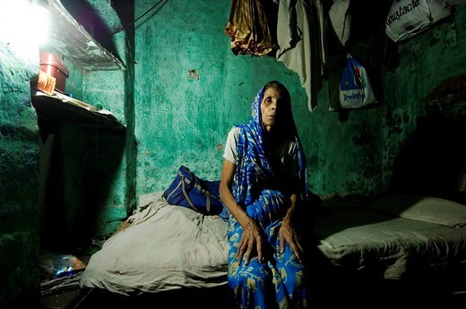 Stock Photo: 1848-106068 Shushila Devi, 70, has tuberculosis and lives in a small, dark room that resembles a cave. She is a widow and her daughter is married and lives far away. Shushila lives from food donations from her neighbours or by begging. Social worker Fahim, who works