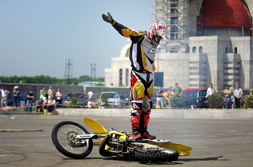 Motorcyclist standing on a racing motorcycle, greeting audience : Stock Photo