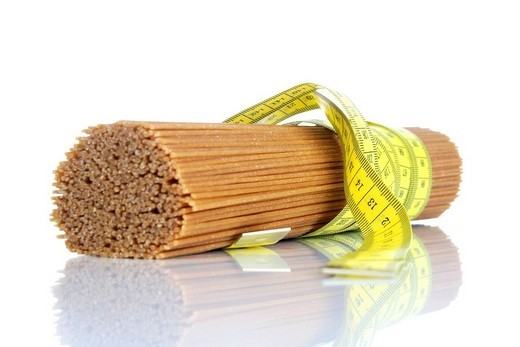 Tape measure, measuring tape tied around spaghetti : Stock Photo