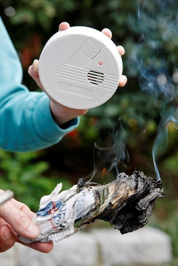 Stock Photo: 1848-106771 Man demonstrating the function of a smoke detector with the help of a burning, fuming piece of paper, Germany, Europe