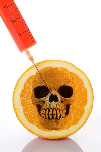 Syringe in orange, symbolic image for genetically modified foods : Stock Photo