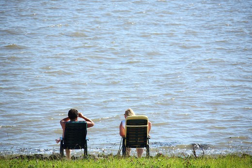 Couple sitting near the water, mouth of the Weser River, Lower Saxony, Germany, Europe : Stock Photo