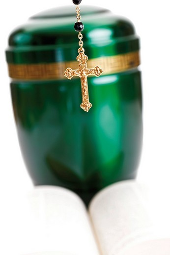 Stock Photo: 1848-112007 Opened Bible and rosary set in front of a green urn
