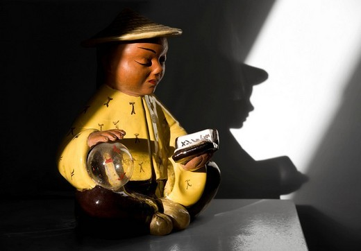Chinese figurine, ceramic figur in a harsh streak of light, reading, shadows : Stock Photo