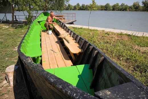 Stock Photo: 1848-112678 A man painting his row boat with fresh green paint in Wylkowe, Danube Delta, Ukraine, Eastern Europe
