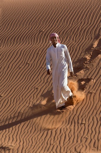 Stock Photo: 1848-113989 Bedouin climbing down a sand dune, ripples, laughing, Wadi Rum, Jordan, Middle East