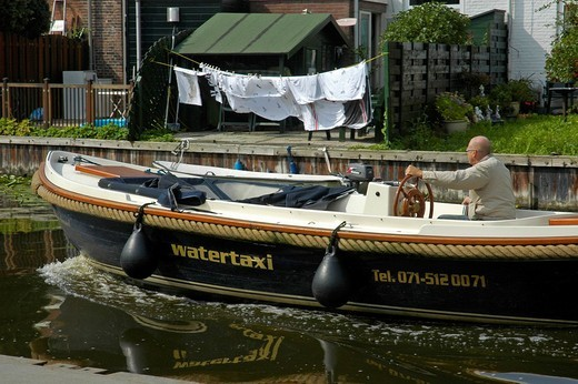 Water cap with driver in a canal, with hung up clothes in the background, Leiden, South Holland, Holland, The Netherlands : Stock Photo