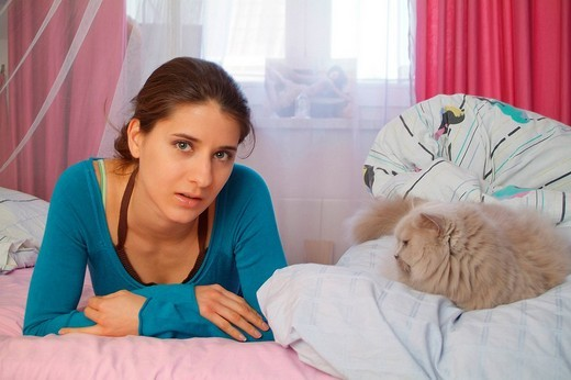 Young with her cat on the bed : Stock Photo