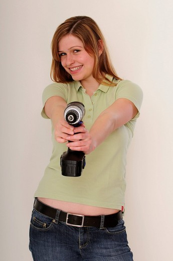 Young long_haired woman wearing green polo shirt holding a power drill : Stock Photo