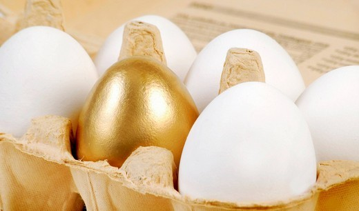 Golden egg in a carton of white eggs : Stock Photo