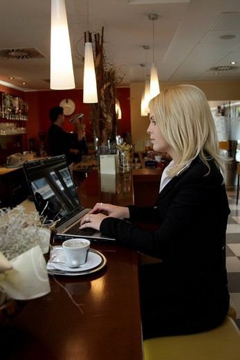 Business woman with laptop in a coffeehouse : Stock Photo