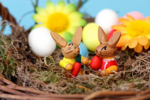 Two wooden Easter bunnies in basket with decorative flowers : Stock Photo