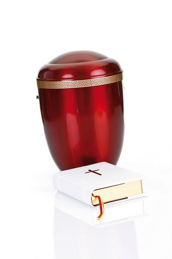 Bible placed in front of a red urn : Stock Photo