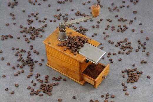 Antique coffee mill with grinding drawer full of freshly ground coffee amidst scattered coffee beans : Stock Photo