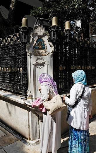 Devout Muslim women drink holy water at a sacred fountain, the courtyard of the Eyuep Sultan Mosque, Eyuep village, Golden Horn, Istanbul, Turkey : Stock Photo