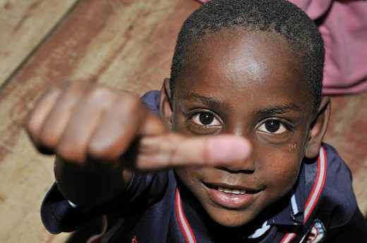 Dark_skinned boy giving an ok sign with his thumb, slums of Alto de Cazuca, Soacha, Bogotá, Columbia : Stock Photo