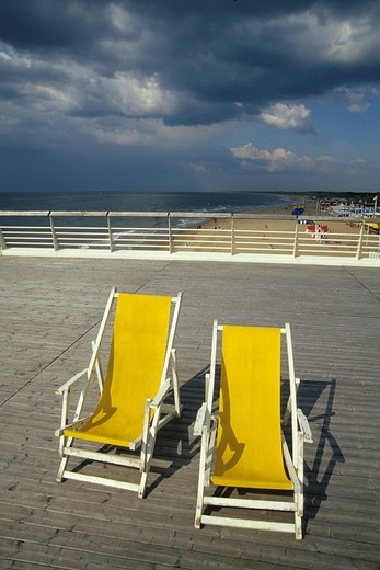 Stock Photo: 1848-124584 Two yellow deckchairs on De Scheveningse Pier, view over the beach of Scheveningen, a sophisticated seaside resort neighbouring Den Haag on the Dutch North Sea coast, province of South Holland, Zuid Holland, the Netherlands, Europe