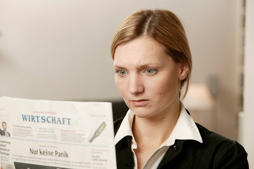 Shocked blonde woman reading a newspaper : Stock Photo