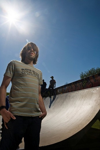 Young man standing in front a skateboard ramp : Stock Photo