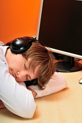 Young man sitting at desk in front of computer, wearing headphones, listening to music with his eyes closed : Stock Photo