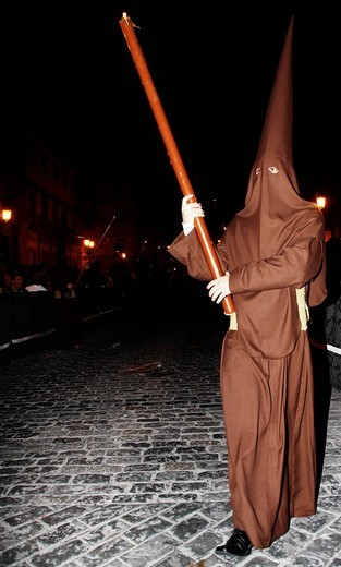 Penitent dressed in brown penitential robe nazareno carrying large candle at night, Semana Santa, Holy Week Procession, Huelva, Andalusia, Spain : Stock Photo