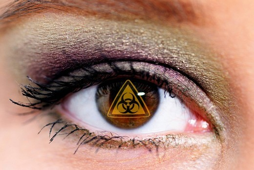 Brown eye of a woman with the sign for biohazard, symbolic picture for genertic engineering : Stock Photo