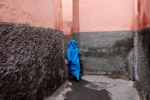 Woman cloaked in a light blue djellaba disappearing mysteriously down a narrow alley, Medina, Morocco, North Africa : Stock Photo