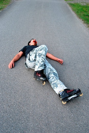 Dangerous sport, in_line skater on the floor after fall, motionless : Stock Photo