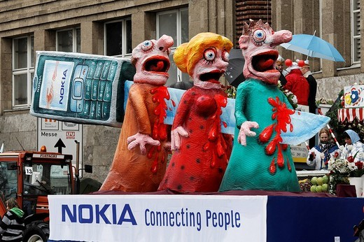 Stock Photo: 1848-133734 Knife impaling three paper_maché figures, its hilt a Nokia phone, political caricature, Carnival Mardi Gras parade in Duesseldorf, North Rhine_Westphalia, Germany, Europe