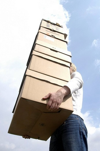 Man carrying a stack of cardboard boxes : Stock Photo