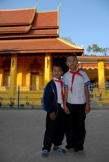 Two pupils standing in front of the yellow_painted Wat Mixay Buddhist Temple, Vientiane, Laos, Asia : Stock Photo
