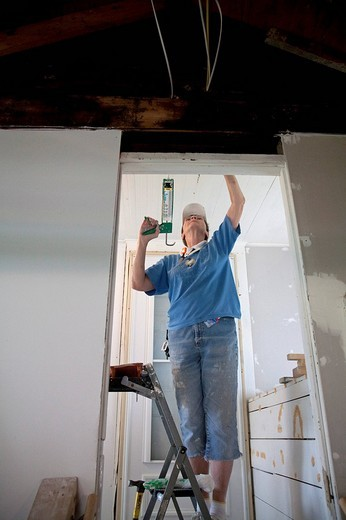 Stock Photo: 1848-134833 Volunteer from the United Methodist NOMADS group repair housing damaged in the 2008 Iowa flood, the NOMADS are retirees who volunteer their services for disaster recovery and other programs, Cedar Rapids, Iowa, USA