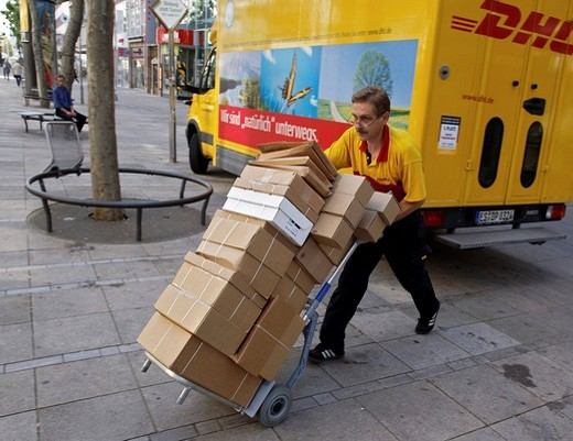 Parcel carrier Michael Meindel balancing a stack of packages across the street with his cart for the Deutsche Post German mail in downtown Stuttgart, Baden_Wuerttemberg, Germany, Europe : Stock Photo
