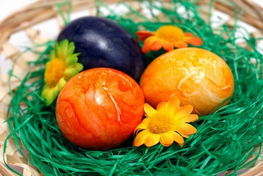 Painted Easter eggs in basket with decorative flowers : Stock Photo