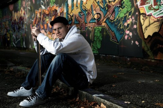 Young man with a skateboard in front of a graffiti wall : Stock Photo