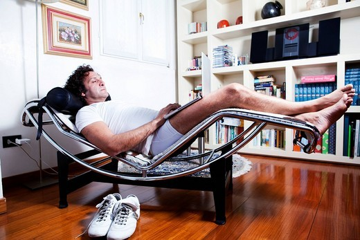 Man in underwear relaxing on a long chair with laptop : Stock Photo