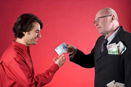 Rich businessman with full pockets offering young man money : Stock Photo
