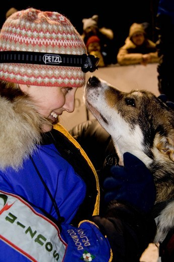 Stock Photo: 1848-137887 Young woman cuddling a sled dog, Yukon Quest Sled Dog Race finish, Whitehorse, Yukon Territory, Canada