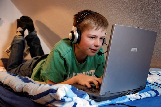 Boy, 13, working with his computer at home in his bedroom while lying on his bed, surfing the Internet on a chat forum and wearing a headset to communicate with other chat users : Stock Photo