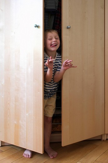 Little boy hiding in a cupboard and playing monster : Stock Photo